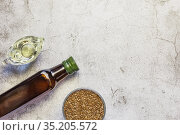 Linseed oil in a bottle, flax seeds, salad dressing in a gravy boat a source of omega-3 antioxidants and fatty acids on a table on a natural gray concrete background top view. Стоковое фото, фотограф Светлана Евграфова / Фотобанк Лори
