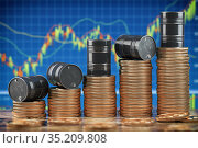 Oil barrels on stack of golden coins. Growth rise of oil stock prices. Стоковое фото, фотограф Maksym Yemelyanov / Фотобанк Лори
