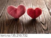 Wool handmade hearts stand on the brown textured wooden boards. Стоковое фото, фотограф Георгий Дзюра / Фотобанк Лори
