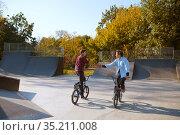 Two bmx bikers, training on ramp in skatepark. Стоковое фото, фотограф Tryapitsyn Sergiy / Фотобанк Лори