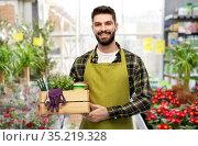 happy gardener or seller with box of garden tools. Стоковое фото, фотограф Syda Productions / Фотобанк Лори