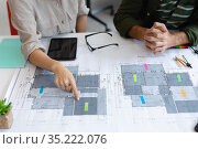 Midsection of diverse male and female colleague looking at blueprints and discussing. Стоковое фото, агентство Wavebreak Media / Фотобанк Лори