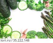 frame of green vegetables broccoli, arugula, cucumber, asparagus and garlic on white background. Стоковое фото, фотограф Татьяна Яцевич / Фотобанк Лори