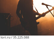 Silhouette of bass guitar player with microphone. Стоковое фото, фотограф EugeneSergeev / Фотобанк Лори