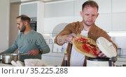 Multi ethnic male same sex couple preparing food together in kitchen. Стоковое видео, агентство Wavebreak Media / Фотобанк Лори