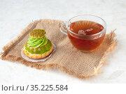 Shu cake with pistachio cream and tea on a linen napkin on the table. Стоковое фото, фотограф Катерина Белякина / Фотобанк Лори