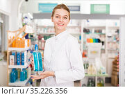 Smiling young pharmacist ready to assist in choosing at counter in pharmacy. Стоковое фото, фотограф Яков Филимонов / Фотобанк Лори
