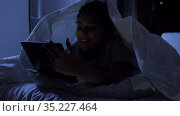 woman with tablet pc under blanket in bed at night. Стоковое видео, видеограф Syda Productions / Фотобанк Лори