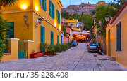Athens, Greece - September 20, 2019: A street in Plaka district on the slope of The Acropolis hill in Athens at dusk. Редакционное фото, фотограф Роман Сигаев / Фотобанк Лори