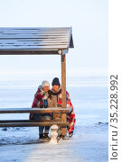 Two frozen girlfriends wrapping with red scarf sitting on wooden bench and drinking hot beverages from thermo mugs for warming up, winter sea beach. Стоковое фото, фотограф Кекяляйнен Андрей / Фотобанк Лори