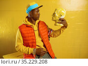 Stylish rapper poses in studio with yellow tones. Стоковое фото, фотограф Tryapitsyn Sergiy / Фотобанк Лори