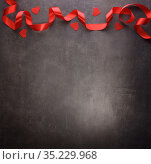 Valentine's Day. Postcard with a border of bright red ribbon and small hearts on a dark background. Top view. Стоковое фото, фотограф Сергей Молодиков / Фотобанк Лори