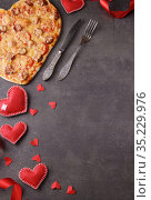 Romantic dinner, pizza heart, bright red hearts and cutlery. Vertical. Top view. Blank space for inscription. Стоковое фото, фотограф Сергей Молодиков / Фотобанк Лори