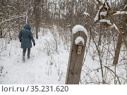 Detroit, Michigan - A hiker in the snow passes a trail marker on ... Редакционное фото, фотограф Jim West / age Fotostock / Фотобанк Лори