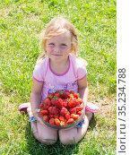 Девочка держит в руках спелую сочную красную ароматную клубнику. The girl holds a ripe juicy red fragrant strawberry in her hands. Стоковое фото, фотограф Мария / Фотобанк Лори