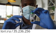 Portrait of african american doctor wearing face mask holding covid-19 vaccine and syringe at home. Стоковое видео, агентство Wavebreak Media / Фотобанк Лори