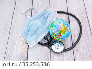 Глобус, фонендоскоп и медицинская маска. Всемирная эпидемия. Стоковое фото, фотограф Наталья Осипова / Фотобанк Лори