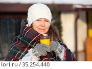 European woman in woollen gloves and checkered scarf holds a yellow paper cup of coffee on the winter city street. Hot and warming beverage in winter season. Стоковое фото, фотограф Кекяляйнен Андрей / Фотобанк Лори