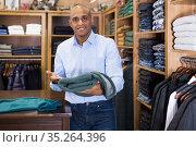 Seller offering suit jacket in menswear boutique. Стоковое фото, фотограф Яков Филимонов / Фотобанк Лори