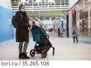 Caucasian mother with her little daughter sitting in children carriage walking in a shopping mall, adult woman wearing face mask. Стоковое фото, фотограф Кекяляйнен Андрей / Фотобанк Лори
