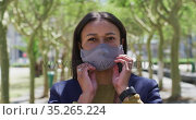 Portrait of african american woman putting on face mask looking at camera in street. Стоковое видео, агентство Wavebreak Media / Фотобанк Лори