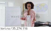 Mixed race female english teacher standing at a whiteboard giving an online lesson to camera. Стоковое видео, агентство Wavebreak Media / Фотобанк Лори