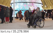 A young woman with grey dreadlocks in a wheelchair at a bright Christmas celebration outdoors - drinking coffee from the cup. Стоковое видео, видеограф Константин Шишкин / Фотобанк Лори