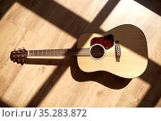 close up of acoustic guitar on wooden floor. Стоковое фото, фотограф Syda Productions / Фотобанк Лори