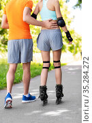 happy couple with roller skates riding outdoors. Стоковое фото, фотограф Syda Productions / Фотобанк Лори