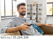 happy man with remote control watching tv at home. Стоковое фото, фотограф Syda Productions / Фотобанк Лори