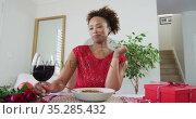 Mixed race woman on a valentines date video call, drinking wine. Стоковое видео, агентство Wavebreak Media / Фотобанк Лори