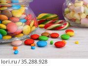 Разноцветные конфеты в стеклянных банках на белом столе. Крупный план. Сиреневый фон. Стоковое фото, фотограф ирина реброва / Фотобанк Лори