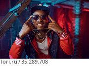 Smiling rapper with gold chain posing in studio. Стоковое фото, фотограф Tryapitsyn Sergiy / Фотобанк Лори