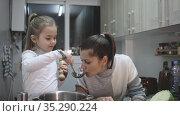 Happy mother and little daughter preparing soup together at home, cut vegetable. Стоковое видео, видеограф Яков Филимонов / Фотобанк Лори