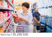 Mature woman examines rose towels in linen section of supermarket. Стоковое фото, фотограф Татьяна Яцевич / Фотобанк Лори