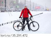 Portrait of an adult man with mountain bicycle standing on snowy bike lane on urban street, winter season with snowfall. Стоковое фото, фотограф Кекяляйнен Андрей / Фотобанк Лори