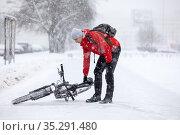 Bicyclist raises the fallen bike from slippery road after crash, person riding a bicycle in town at winter season. Стоковое фото, фотограф Кекяляйнен Андрей / Фотобанк Лори