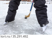 Close up view at black puck and hockey skates on lake ice, teenage male legs, rear view. Стоковое фото, фотограф Кекяляйнен Андрей / Фотобанк Лори
