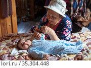 Elderly Caucasian grandmother talking with newborn grandchild lying on bed, holding baby hand and smiling. Стоковое фото, фотограф Кекяляйнен Андрей / Фотобанк Лори