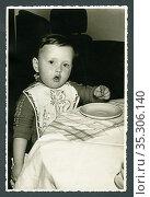 Europa, Deutschland, Hamburg, kleines Kind beim Essen, in den 1950er... Редакционное фото, фотограф Historisches Auge Ralf Feltz / age Fotostock / Фотобанк Лори