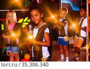 Cute little mulatto girl standing with laser pistol in dark lase. Стоковое фото, фотограф Яков Филимонов / Фотобанк Лори
