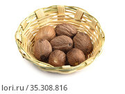 Nutmeg in bamboo basket isolated on white background. Стоковое фото, фотограф Dipak Chhagan Shelare / easy Fotostock / Фотобанк Лори