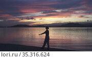 A young slender sports woman walks along the coast of the tropical sea at sunrise, a girl makes a sports warm-up. Стоковое видео, видеограф Куликов Константин / Фотобанк Лори