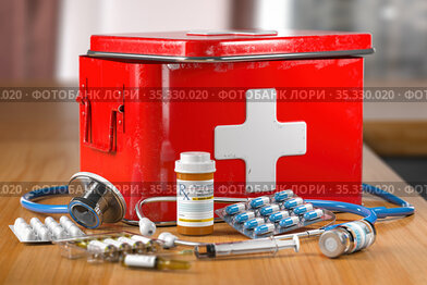 Open first aid kit with stethoscope, pills and smedicationon the table.