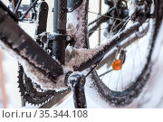 Close up view of bicycle sprocket, chain and treadle covered with ice and snow at winter time, bicycling at winter. Стоковое фото, фотограф Кекяляйнен Андрей / Фотобанк Лори