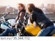 Two European women motorcyclists talking cheerfully while sitting on their motorcycles. Стоковое фото, фотограф Кекяляйнен Андрей / Фотобанк Лори