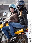 Girlfriend a passenger sitting behind female motorcyclist on a motorbike, cheerful females riding on the urban streets. Стоковое фото, фотограф Кекяляйнен Андрей / Фотобанк Лори
