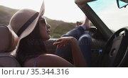 African american woman sitting with her feet on the window of convertible car. Стоковое видео, агентство Wavebreak Media / Фотобанк Лори