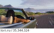 African american woman driving along country road in convertible car. Стоковое видео, агентство Wavebreak Media / Фотобанк Лори