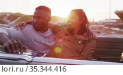 African american couple embracing each other while sitting in the convertible car on the road. Стоковое видео, агентство Wavebreak Media / Фотобанк Лори